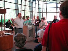 Conference participants gather around a uniformed employee of Parks Canada for a tour of the Visitor Centre exhibit in 2008