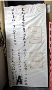 """The dedication scroll as originally received. The letter """"A"""" is unrelated to the scroll but had fallen behind the broken glass and hadn't been removed at the time the photo was taken. Photo: Gina Leigh."""
